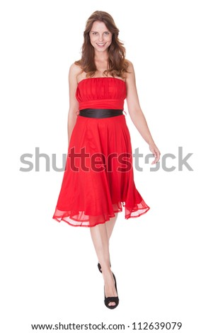Glamorous elegant woman in a trendy red dress walking towards the camera with a lovely smile isolated on white - stock photo