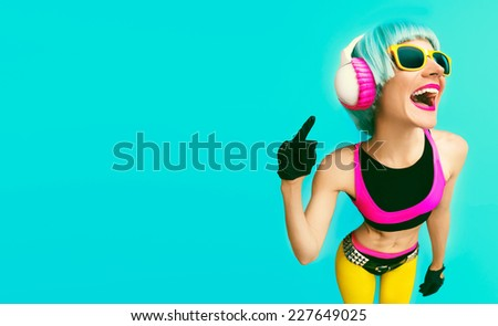 Glamorous Fashion DJ Girl in bright clothes on a blue background listening to Music. - stock photo