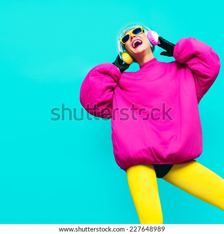 Glamorous Fashion Model in bright clothes on a blue background listening to Music. All shades of music.