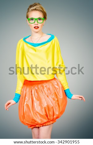 Glamorous fashion model posing in vivid colourful clothes and glasses. Bright fashion. Optics, eyewear. Studio shot. - stock photo