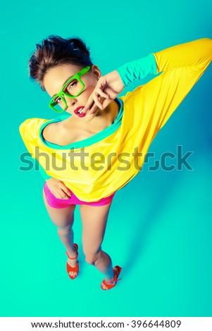 Glamorous fashion model posing in vivid colourful clothes and glasses. Bright fashion. Optics, eyewear. Studio shot. - stock photo