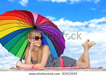 glamorous girl in retro style by color umbrella on the beach - stock photo
