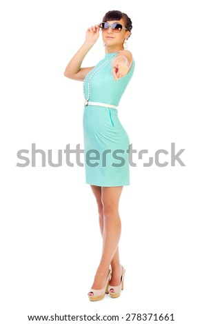 Glamorous girl in turquoise dress shows pointing gesture isolated - stock photo