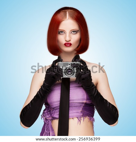 Glamorous girl, vintage vamp style, dressed in a necktie and long gloves, shooting with an old vintage photo camera on blue background. - stock photo