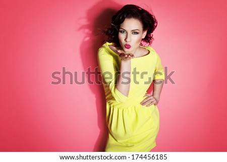 Glamorous girl wearing yellow dress, sending a kiss - stock photo