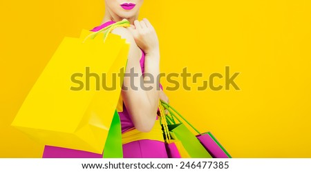 Glamorous Lady with shopping on bright yellow background - stock photo