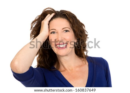 Glamorous middle aged woman smiles to the camera, whilst pushing her hair back from her face - stock photo