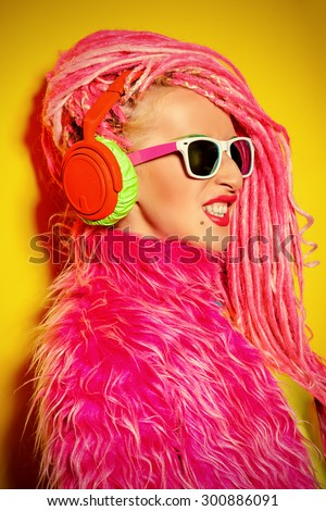 Glamorous modern DJ girl wearing bright clothes, headphones and bright dreadlocks. Disco, party. Bright fashion. - stock photo