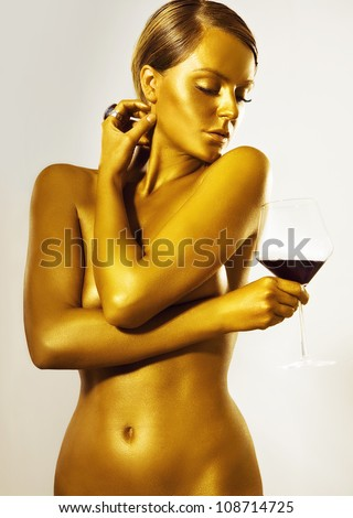 glamorous naked girl painted in gold color with a glass of wine in hand  - stock photo