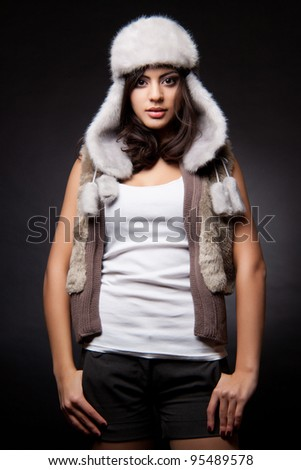 glamorous portrait of a beautiful young woman in a fur vest - stock photo