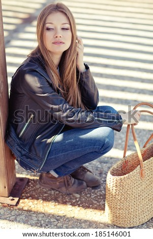 glamorous portrait of young beautiful woman in a leather jacket