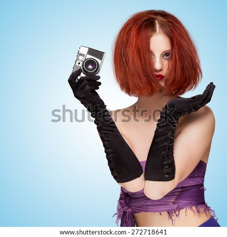 Glamorous seductive girl, wearing long gloves and disheveled hairstyle, holding an old vintage photo camera on blue background. - stock photo
