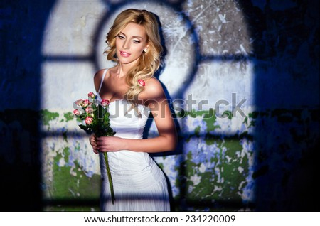 Glamorous sexy blonde girl in a white dress with roses on the background wall, illuminated by the light - stock photo