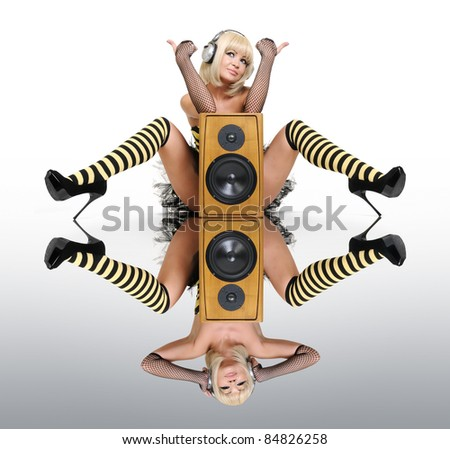 Glamorous sexy girl with speakers on the mirror with a full different reflection, sound concept - stock photo