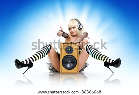 Glamorous sexy party girl in headphones with speaker, happy sound concept - stock photo