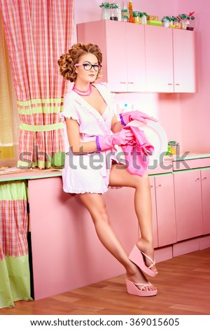 Glamorous sexy pin-up girl washing the dishes on her pink kitchen. Fashion.
