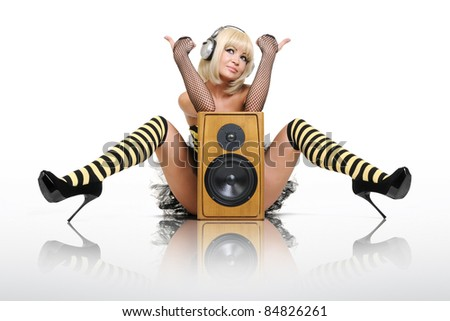 Glamorous sexy young girl in headphones with wooden speaker, sound concept - stock photo