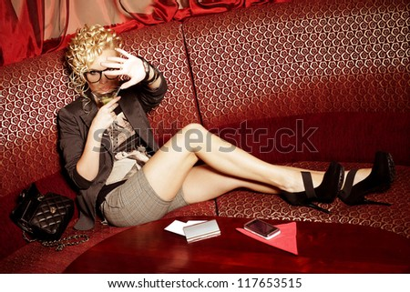 glamorous superstar with cocktail hiding from paparazzi in restaurant. indoor shot - stock photo