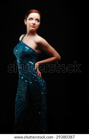 Glamorous woman in a blue sparkly dress posing