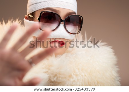 Glamorous woman in bandage trying to clock out camera - stock photo