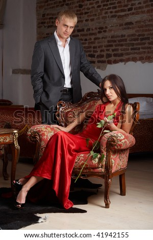 Glamorous woman in red dress sitting on a chair and man standiing near - stock photo