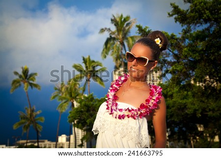 Glamorous woman in white dress enjoying the perfect sunset on tropical resort. Summer luxury vacation in Hawaii. Honolulu, HI, United States Island of Oahu - stock photo