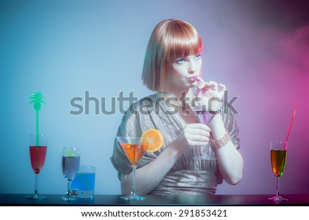 Glamorous Woman with Red Hair Wearing Shiny Retro Gown and Sipping Cocktail Drink from Straw, Standing at Bar in Disco Night Club