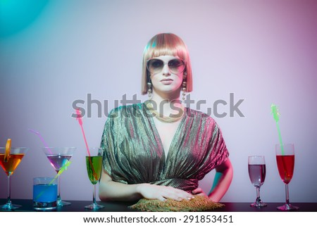 Glamorous Woman with Red Hair Wearing Sunglasses and Shiny Retro Gown Standing with Hand on Hip at Cocktail Covered Bar in Disco Night Club