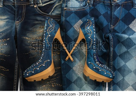 Glamorous women's fashion, jeans, shoes in rhinestones, lying on jeans, as background