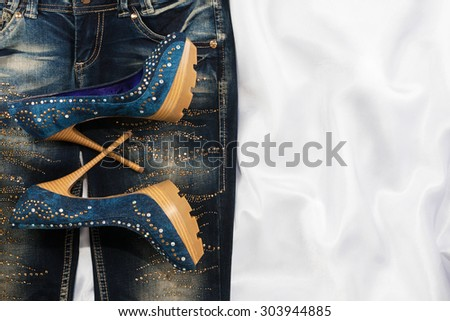 Glamorous women's fashion, jeans, shoes in rhinestones, lying on white silk - stock photo