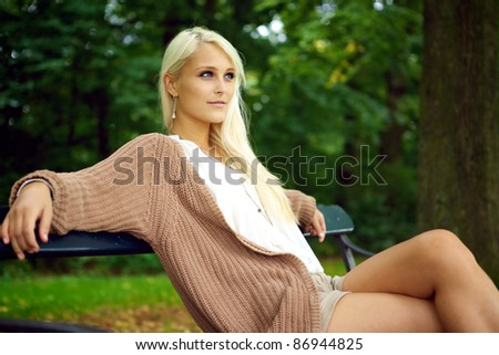 Glamorous young blonde lady relaxing on a park bench enjoying nature, healthy wellbeing. - stock photo