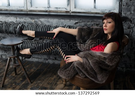 Glamorous young lady in fur coat posing by the window in a vintage interior, studio shot - stock photo
