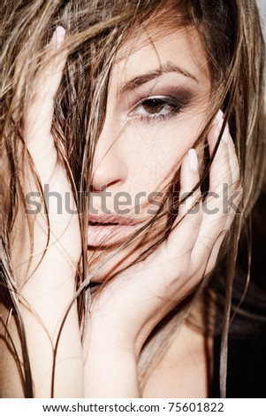 Glamorous young lady touching her hair near white wall - stock photo