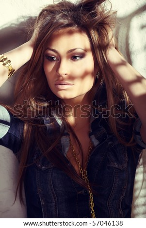 Glamorous young lady touching her hair near white wall with cross processing toning - stock photo