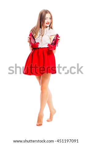 Glamorous young smiling woman in a red skirt puts red patent leather shoes, isolated on white background.