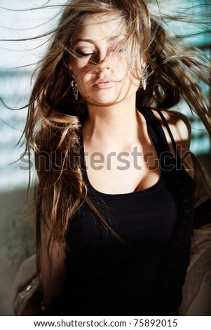 Glamorous young woman in near a wall - stock photo