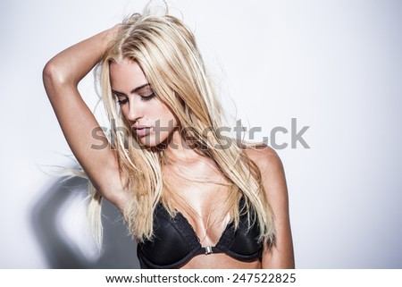 Glamorous young woman in sexy lingerie posing near a white wall - stock photo