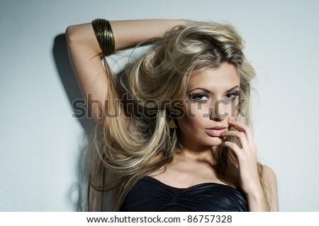 Glamorous young woman near white wall - stock photo