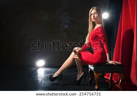 Glamorous young woman  with cigarette wearing red dress sitting on a stool on stage.  - stock photo