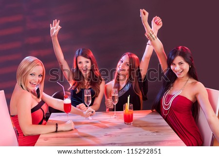 Glamorous young women celebrating in a nightclub sitting around a table laughing and raising their arms in the air in jubilation - stock photo