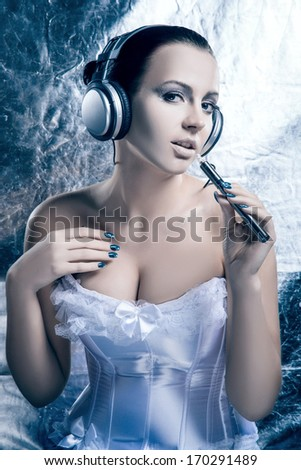 Glamour and bizarre portrait of young and beautiful woman smoking the electronic cigarette and listening to the music over creative winter background - stock photo