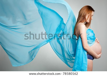 Glamour and style of young pensive pregnant woman with blue material - stock photo