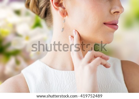 glamour, beauty, jewelry and luxury concept - close up of beautiful woman face with gold and diamond earring over natural spring lilac blossom background