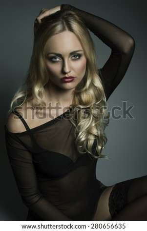 glamour blonde girl with long wavy hair and transparent dark underwear shirt, black bra and sexy stockings. Sitting and looking in camera with charming expression  - stock photo