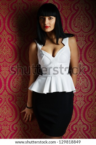 Glamour brunette woman portrait in black and white dress in studio - stock photo