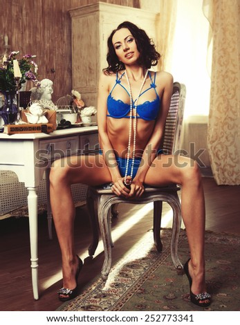 Glamour brunette woman wearing lingerie posing at home - stock photo