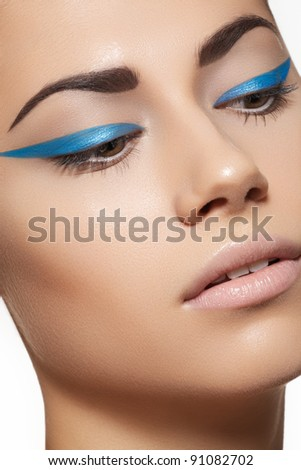 Glamour close-up portrait of beautiful woman model face with winged bright blue eyeliner make-up, clean skin on white background - stock photo