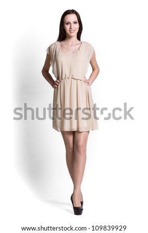 Glamour girl in beige dress on white