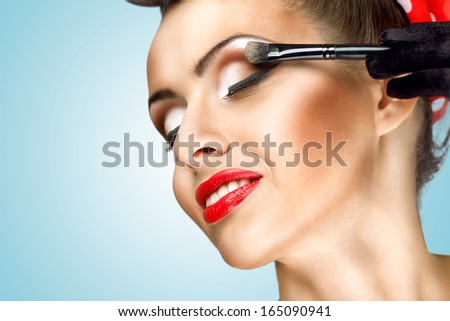 Glamour girl with fashion makeup painting her cheek with brush.