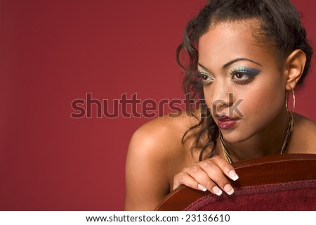 Glamour Headshot of  young dark skinned female with dramatic makeup sitting on red chair meditating, thinking and looking away from camera - stock photo